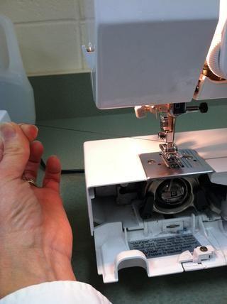 Tire de la bobina de hilo a través de la placa de la aguja de la siguiente manera: 1). sostener el hilo superior con la mano izquierda.