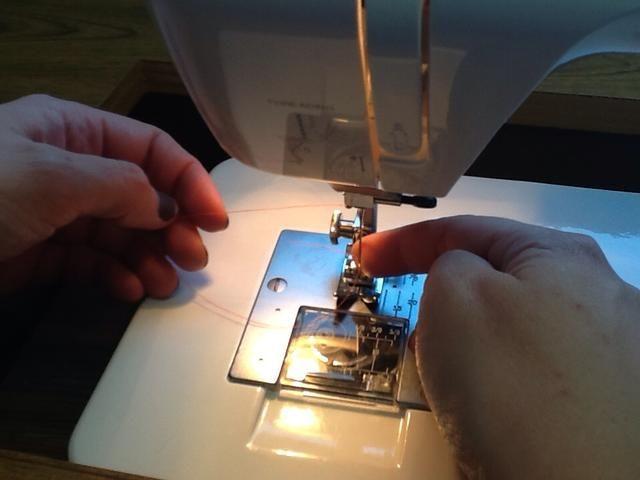 Sujete el hilo hacia la izquierda por lo que doesn't wrap around the needle.