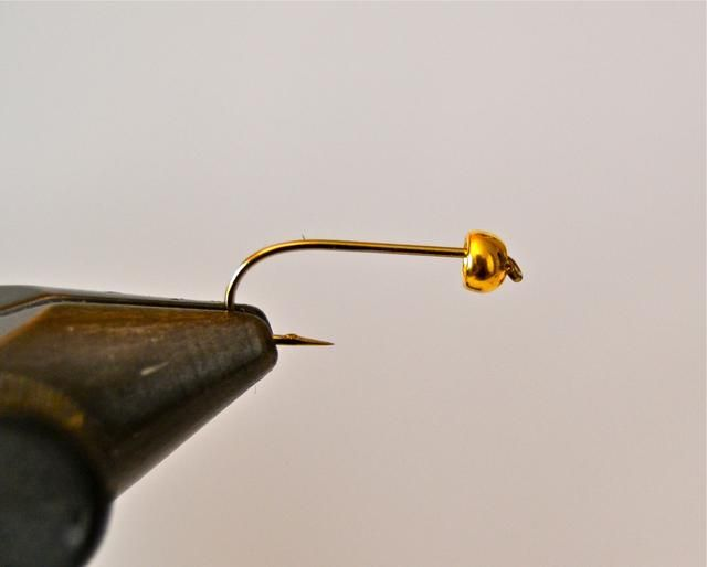 Deslice en un latón o perla de tungsteno (color dorado) sobre el extremo puntiagudo del gancho (lado pequeño agujero primero.) Por esta guía usé un cordón tung 3,8 mm.)