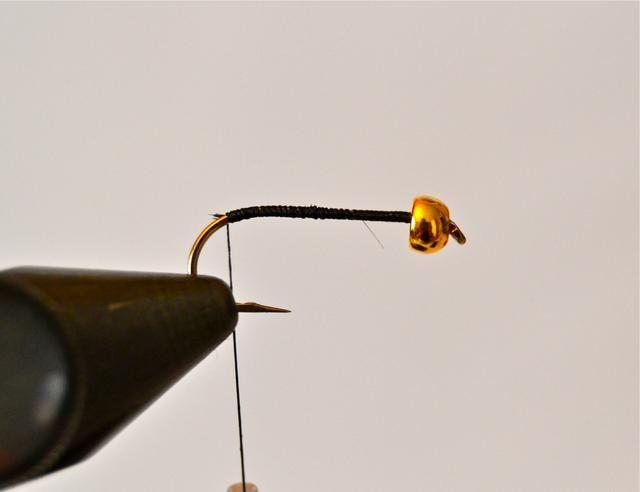 Envolver el hilo negro que cubre el eje desde el extremo de ojo de vuelta a donde el eje comienza a curvarse hacia abajo. Aquí es donde usted'll begin making your goose biot 'tail.'