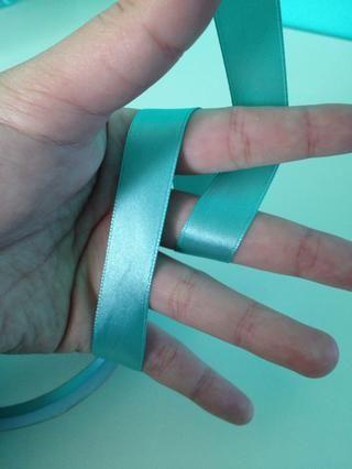 Bucle de la cinta en el lado derecho exterior sobre su segundo dedo y bajo su primero.