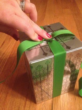 Gire los 2 extremos de la cinta de 90 grados para que se cruzan, creando una X en la parte superior. Dependiendo si're left or right;handed, one end is over the front and the other is over the back of the box.