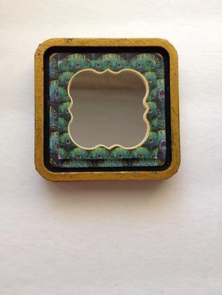 Tome la etiqueta engomada del marco de pavo real desde el paso 17 y adjuntar al espejo.