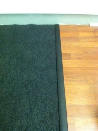 Para acoplar la alfombra con el laminado, He comprado una tira de goma que mantiene todo en su lugar mediante la compresión de la alfombra y el laminado entre el caucho y un respaldo de metal
