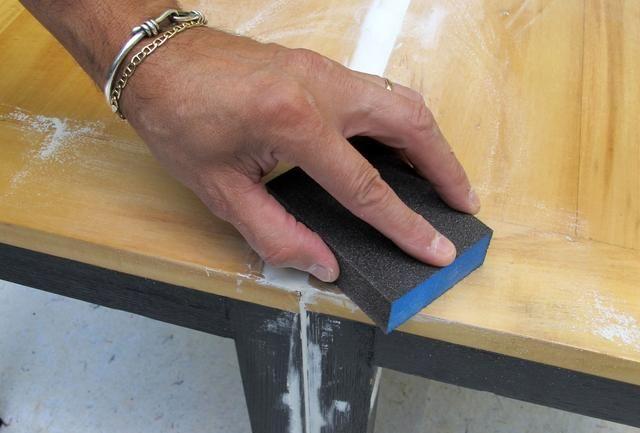 Después de que el parche de la madera se ha secado, arena la superficie de las sillas antes de pintar.