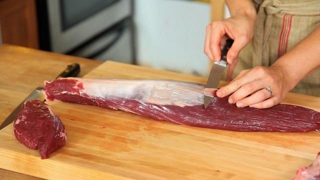 Gire el lomo liso hacia arriba. Para eliminar toda la piel plateada, mantenga el cuchillo en un ángulo contra la carne. Tome la punta de su cuchillo y deslícela lo más cerca que puede debajo de la piel plateada.