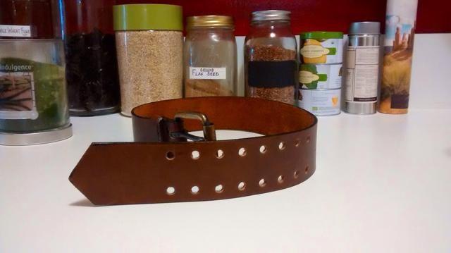 Obtener un cinturón de cuero viejo o cualquier paz de cuero que se puede envolver alrededor del frasco. Tengo esta cinta en la buena voluntad de $ 1.99.