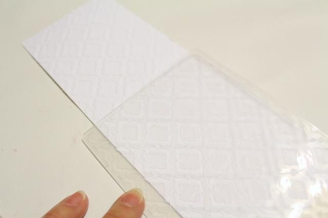 cortar un 3 X 10 pedazo de blanco mate cartulina, poner un extremo en moda Azulejos 2 Embossing Folder y relieve. gire cartulina alrededor, ponga en relieve patrón con el patrón en la carpeta y relieve de nuevo ...