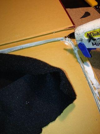 Después de recortar el exceso de papel y pegar las páginas, tomar la tela y un pegamento glun y pegar la tela dentro de la caja. Esto le da a la tableta una superficie suave para tumbarte.