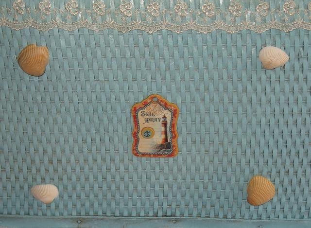 Terminar decorando los lados y esquinas utilizando las piezas de madera aglomerada y conchas de mar. Utilice el panadero's Twine to hang some of the pieces on the corners by gluing the twine and chipboard to the basket.