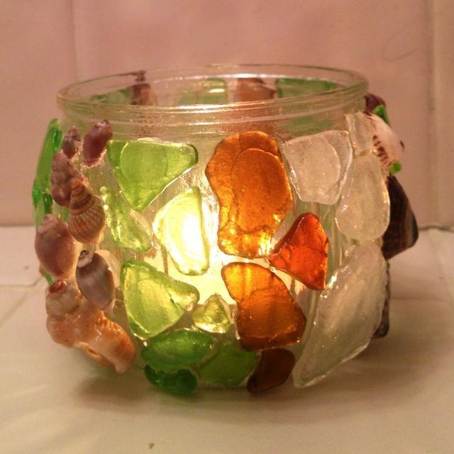 Un frasco con seaglass y conchas marinas caliente pegado y luego recubierta con Mod Podge