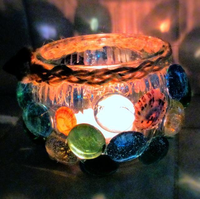 Luces de té brillan maravillosamente a través de cristales de colores y conchas finas