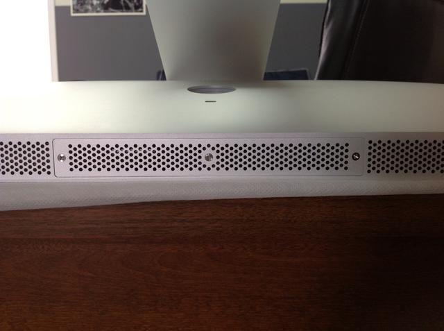 En la parte inferior de la pantalla (bajo iMac soporte) se encuentra una pequeña tapa con 3 tornillos de cabeza Phillips en el mismo.