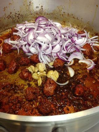 Añadir el chorizo y luego la cebolla y el ajo asado