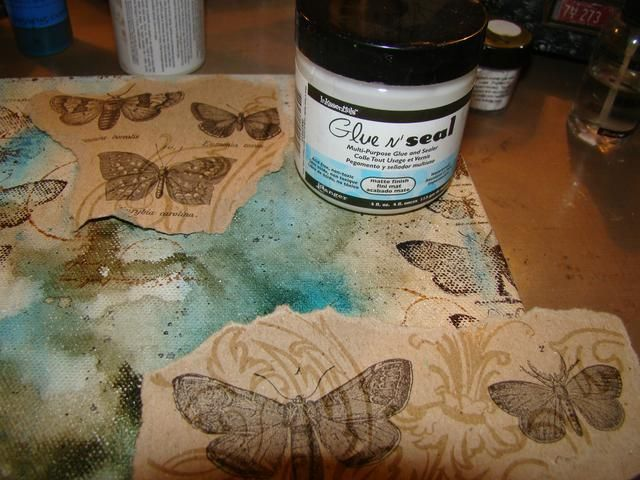 Aplicar sus hojas rasgadas con pegamento N Seal. También puede utilizar Mod Podge. Don't forget to let some of the papers run over the edge of the canvas. We don't want to forget to decorate the edges.