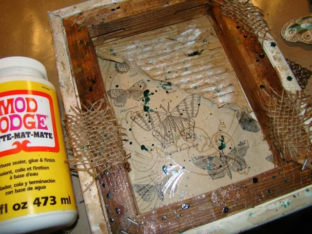 Tome arpillera y aplicar de forma aleatoria a su creación mediante Mod Podge. Deje que se seque. También tomé el brillo Glam y salpicó en la pieza y seco cepillado con pintura blanca acrílica sobre la parte superior.