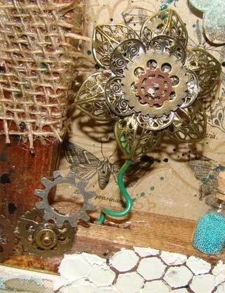 Capa de diferentes flores de metal en la parte superior de uno al otro y añadir ruedas dentadas y engranajes para crear su flor. Pegue el tallo de la flor y de cola a su porción de bastidor de madera de la tela.