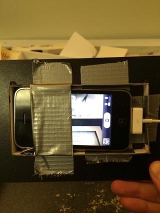 El teléfono está mirando a través del agujero perforado. Observe el fajo de cinta usé como un espaciador para levantar el teléfono un poco.