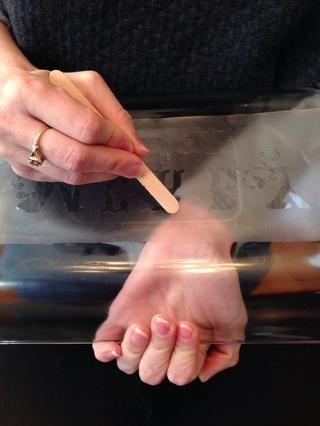 Utilice el palito de madera para frotar más firmemente hacia abajo todos los bordes para que ninguno de la crema de grabado se pone en el papel de contacto.
