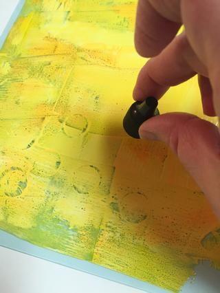 Una vez que los colores se extendieron sobre la placa con la rueda de arte, se utilizó la tapa de una de las botellas de tinta para agregar círculos en la placa. una impresión se hizo y se deja secar antes de continuar.