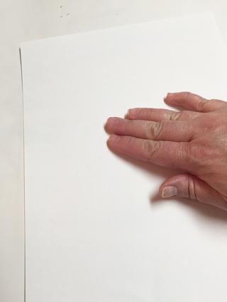 colocar hoja de papel en la parte superior de la placa de entintado y alisar suavemente con los dedos para transferir la tinta. tenga cuidado de no mover el papel.