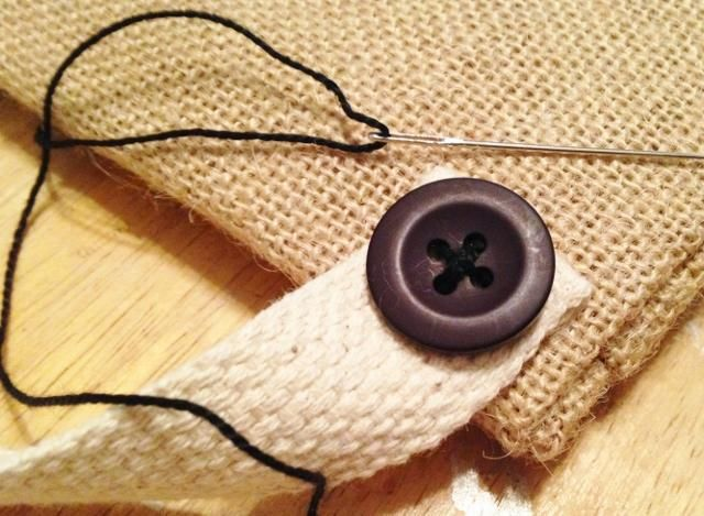 Pegué los extremos de la bandas a la parte posterior de la bolsa, y luego cosido en los botones de la vendimia. me decidí a utilizar una combinación de pegamento y costura para sujetar el mango de forma segura en la arpillera.