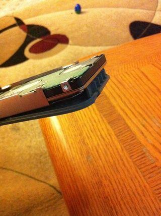 Tire de la unidad de disco duro de distancia desde el cable conectado. Usted tiene que doblar ligeramente la pieza de plástico perforado gris para deslizar la unidad de disco duro como muestra la imagen.