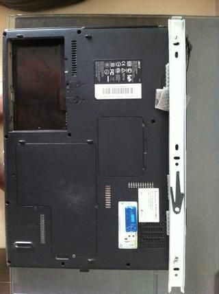 Fijar una parte del canal de deslizamiento en el ordenador portátil con tornillos