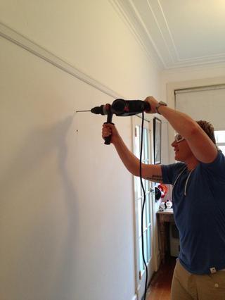 Use un taladro de percusión para perforar agujeros en las marcas de la pared que ha hecho