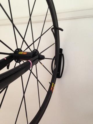 Levante la bicicleta y enganchar el borde de la llanta en el bastidor
