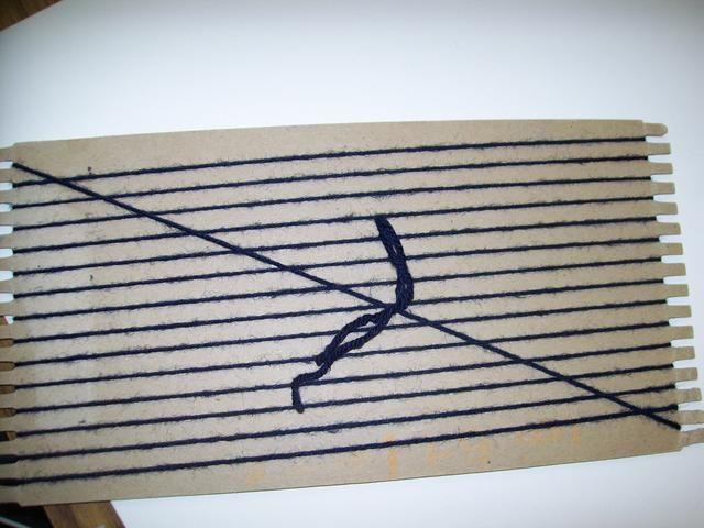 En la parte posterior del telar, atar los extremos del hilo juntos haciendo la urdimbre del telar apretada. La urdimbre es las cuerdas verticales en el telar.