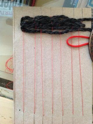 Va a mantener la parte doblada de la cuerda con fuerza y comenzar tejiendo SOBRE DOS cuerdas de urdimbre.
