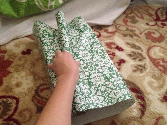 Cubrirá caja, con fuerza, con el papel enrollado