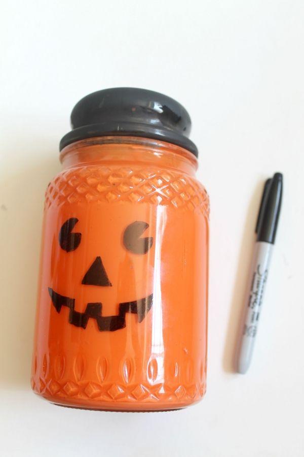 dibujar una cara de la Jack-o-linterna con un Sharpie, ver más a http://artesaniasdebricolaje.ru/mason-jar-crafts-pumpkin-candy-jars