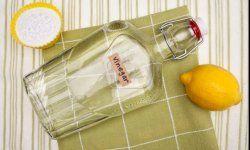 El bicarbonato de sodio, una botella de vinagre y un limón en un paño de cocina.