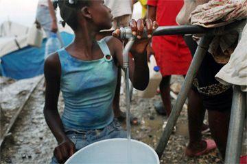 Niña haitiana llenado jarra de agua