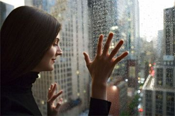 Mujer mirando por la ventana de vidrio