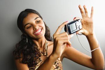 Mujer joven con la toma de la cámara foto de sí misma