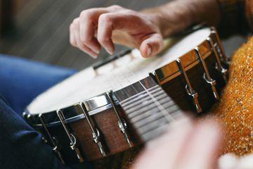 Cerca de las cuerdas del banjo recogiendo mano